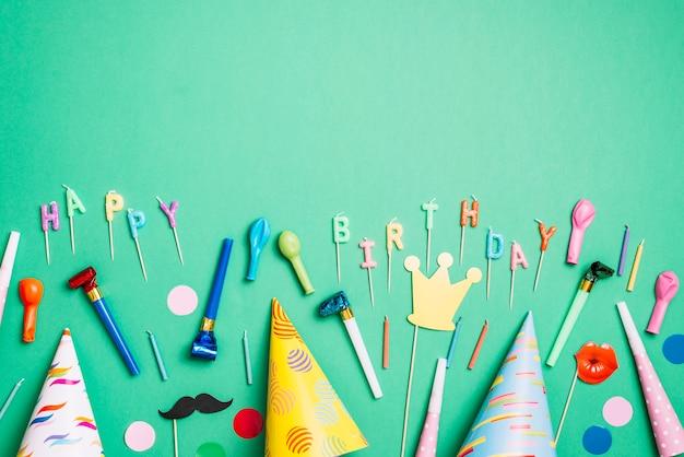 Geburtstagsfeierhintergrund mit partyhüten; requisiten; ballons; hornbläser und kerzen auf grünem hintergrund Kostenlose Fotos