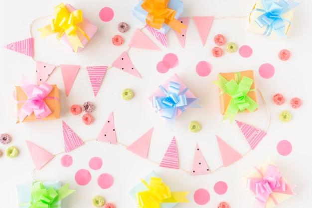 Geburtstagsgeschenke; froot reifen süßigkeiten und party-zubehör auf weißem hintergrund Kostenlose Fotos