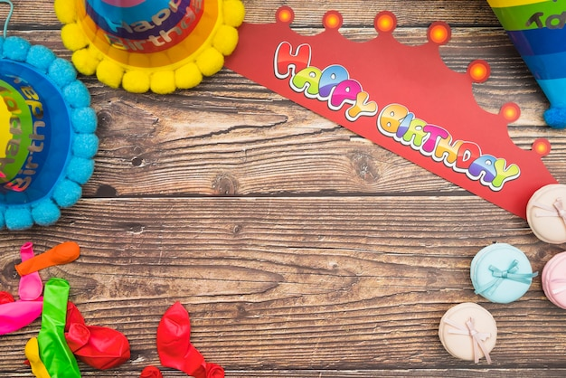 Geburtstagshut; krone; ballons und macarons auf hölzernen hintergrund Kostenlose Fotos