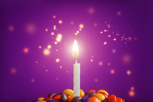 Geburtstagskerze auf köstlichem kleinem kuchen mit süßigkeiten auf hellpurpurnen hintergrund. feiertagsgrußkarte Premium Fotos