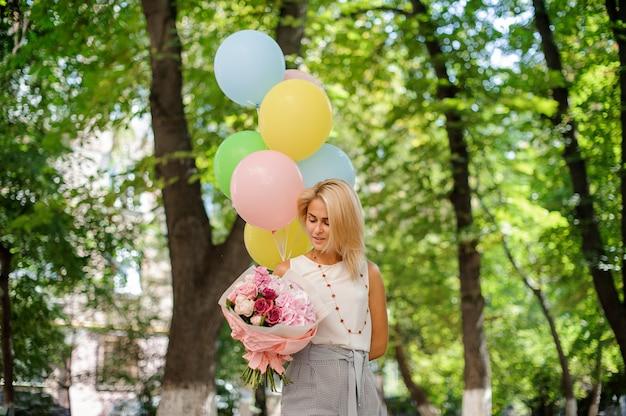 Geburtstagskind mit einem blumenstrauß von hübschen blumen und von ballonen Premium Fotos