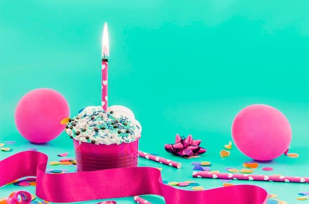 Geburtstagskleiner kuchen mit kerze und ballonen Kostenlose Fotos