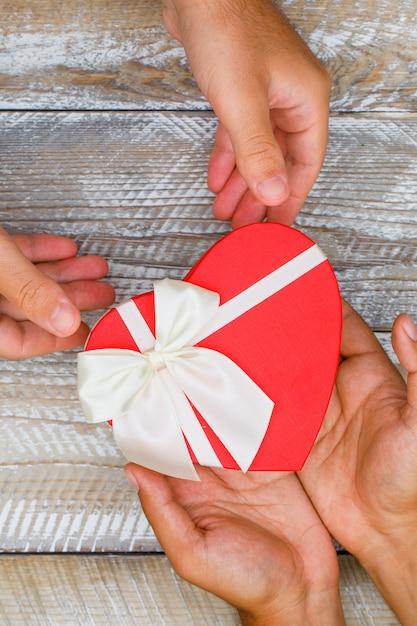 Geburtstagskonzept auf hölzernem hintergrund flach lag. hände geben und empfangen geschenkbox. Kostenlose Fotos