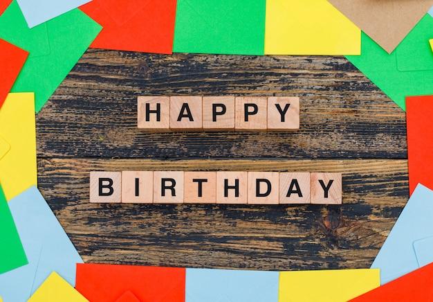 Geburtstagskonzept mit farbigen umschlägen, holzwürfeln auf hölzernem hintergrund flach legen. Kostenlose Fotos
