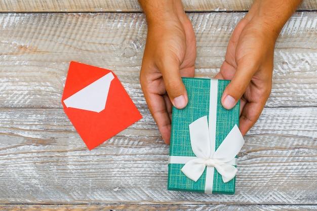 Geburtstagskonzept mit karte im umschlag auf hölzernem hintergrund flach legen. mann vorbei geschenkbox. Kostenlose Fotos