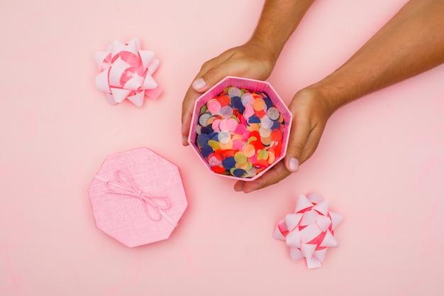 Geburtstagskonzept mit konfetti, bögen auf rosa hintergrund flach legen. hände halten geschenkbox. Kostenlose Fotos