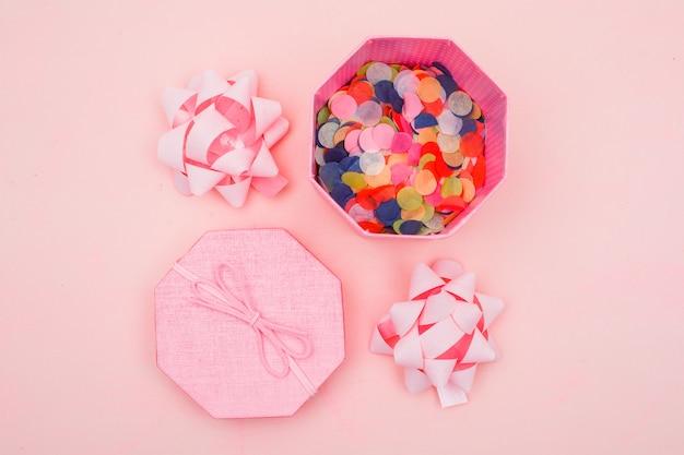 Geburtstagskonzept mit konfetti in geschenkbox, bögen auf rosa hintergrund flach legen. Kostenlose Fotos
