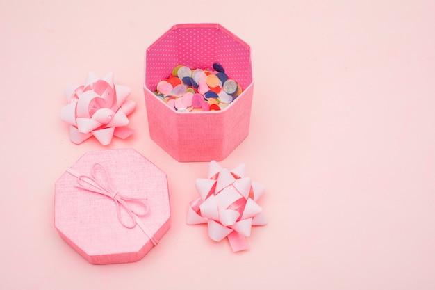 Geburtstagskonzept mit konfetti in geschenkbox, bögen auf rosa hintergrund-hochwinkelansicht. Kostenlose Fotos