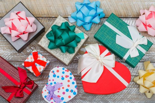 Geburtstagskonzept mit verschiedenen geschenkboxen, bögen auf holzhintergrund flach legen. Kostenlose Fotos