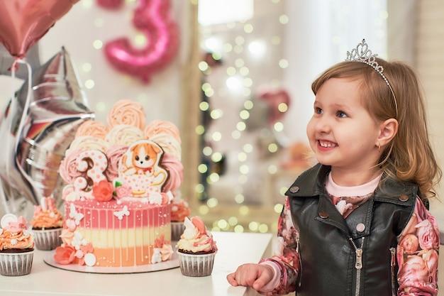 Geburtstagstorte für 3 jahre mit schmetterlingen, lebkuchen-kätzchen mit zuckerguss und der nummer drei dekoriert. Premium Fotos
