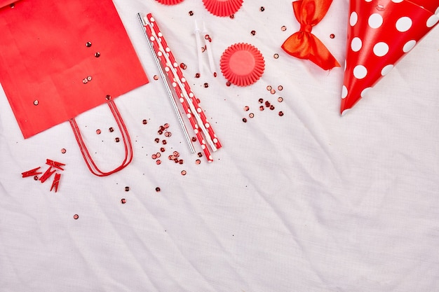 Geburtstagswohnung, draufsicht und kopierraum für text, rahmen oder hintergrund mit roten festivalgegenständen, partyhüten und luftschlangen, geburtstags- oder partygrußkarte Premium Fotos