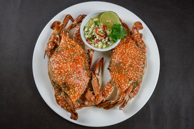 Gedämpfte blaue krabbe auf weißer platte mit würziger meeresfrüchtesoße Premium Fotos