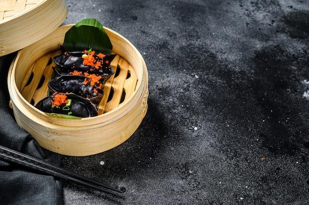 Gedämpfte knödel dim sum im bambusdampfer. schwarzer hintergrund Premium Fotos