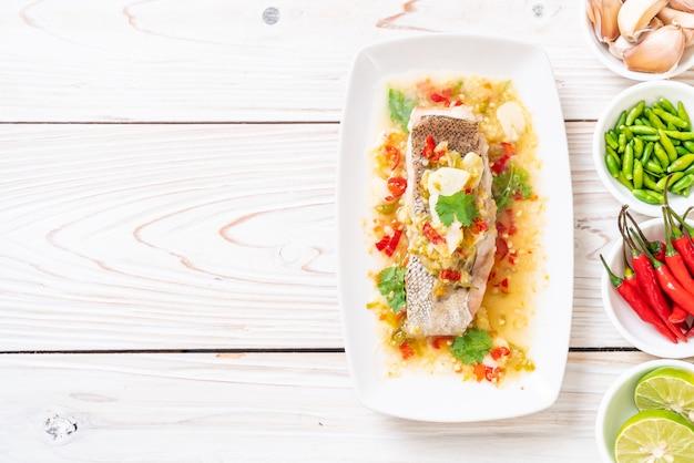 Gedämpftes zackenbarschfilet mit chili-limetten-sauce im limetten-dressing Premium Fotos