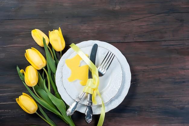 Gedeck für ostern auf einem hölzernen hintergrund Premium Fotos