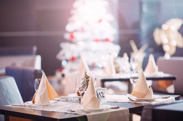 Gedeck im restaurant mit weihnachtsbaum Premium Fotos