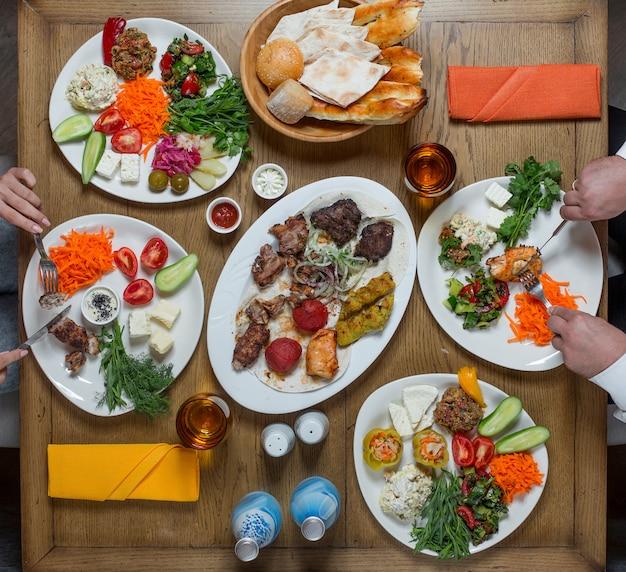 Gedeck in weißen tellern mit fleisch und gemüse, Kostenlose Fotos