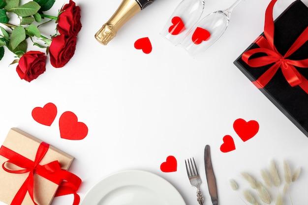 Gedeck, rosen und geschenke auf weißem tisch Premium Fotos