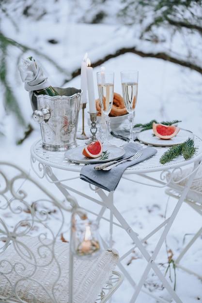 Gedeckter tisch für ein romantisches abendessen mit kerzen, sekt und obst im winterwald Premium Fotos