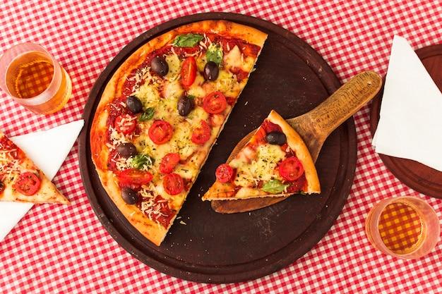 Gediente pizzascheibe auf spachtel über hölzernem kreisbrett gegen tischdeckenhintergrund Kostenlose Fotos