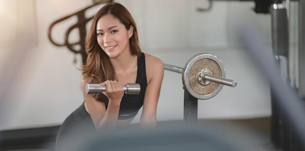 Geeignete anhebende gewichte der asiatischen athletischen frau innerhalb der turnhalle und lächeln an der kamera Premium Fotos