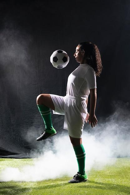 Geeignete frau des erwachsenen, die mit fußball spielt Kostenlose Fotos