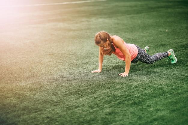 Geeignete frau in heller sportkleidung, zum von burpees auf dem grünen gras zu tun Premium Fotos