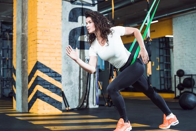Geeignete junge frau, die übung im fitness-club tut Kostenlose Fotos