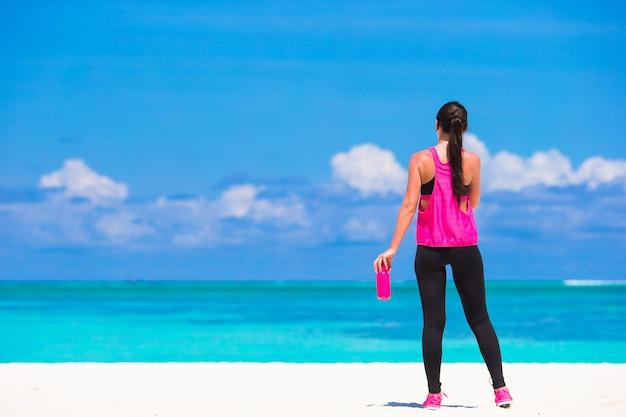 Geeignete junge frau, die übungen auf tropischem weißem strand in ihrer sportkleidung tut Premium Fotos