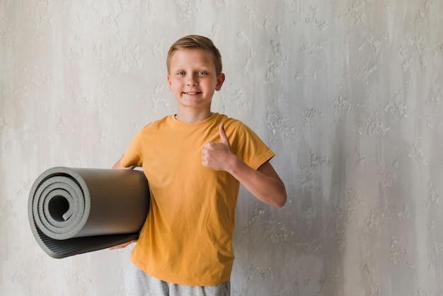 Geeignete lächelnde jungenholding rollte herauf die übungsmatte, die daumen zeigt, herauf zeichen vor konkretem hintergrund Kostenlose Fotos