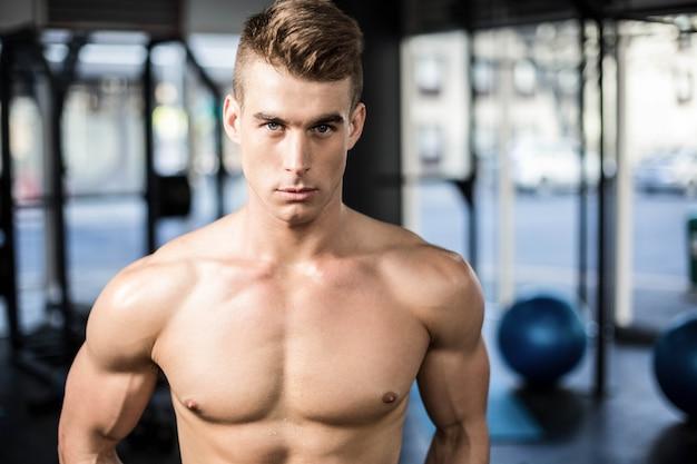 Geeignete muskulöse mannaufstellung hemdlos an der turnhalle Premium Fotos