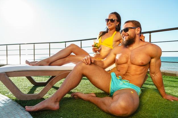 Geeignete muskulöse paare in der badebekleidung, die nahe dem pool sich entspannt Premium Fotos