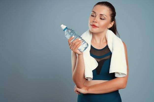 Geeignete sportliche frau, die mineralwasserflasche in ihrer hand hält Premium Fotos