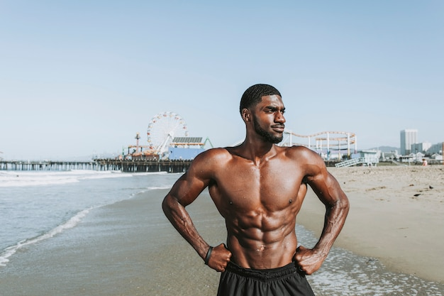 Geeigneter Mann, der am Strand aufwirft Premium Fotos