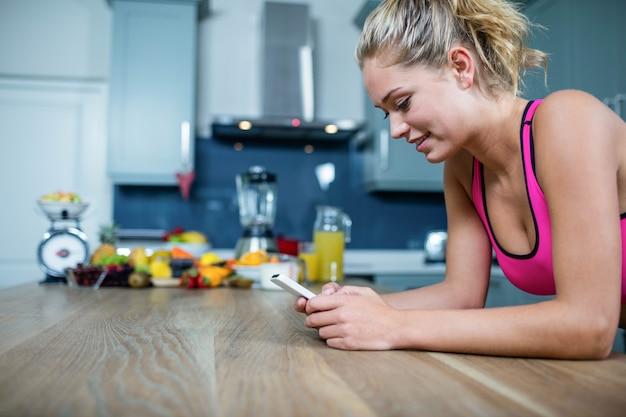 Geeignetes mädchen, das textnachrichten in der küche sendet Premium Fotos