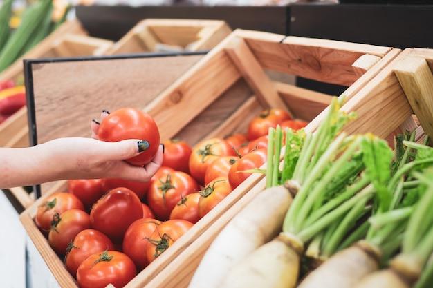Geerntet von den kaufenden früchten der jungen frau am markt des landwirts Premium Fotos
