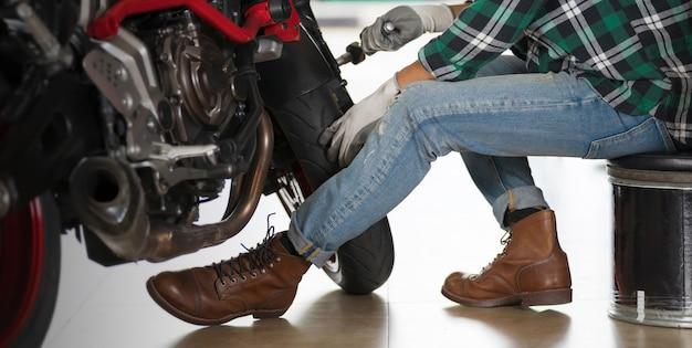 Geerntete ansicht des motorradmechanikers unter verwendung eines schlüssels und eines sockels auf einem motorrad Premium Fotos