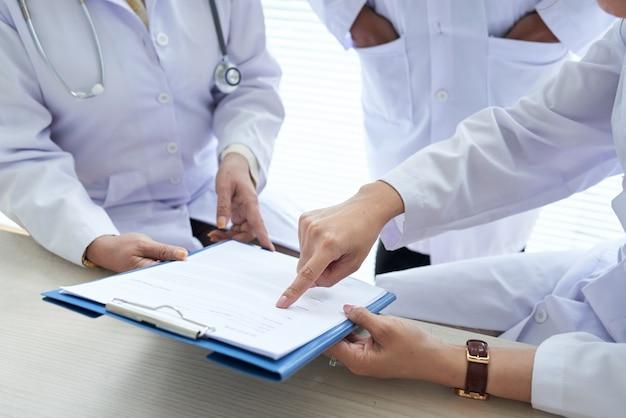 Geerntete doktoren, die medizinisches dokument im team besprechen Kostenlose Fotos