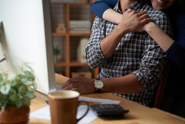 Geerntete frau, die ihren unerkennbaren ehemann mit einer umarmung stützt Kostenlose Fotos