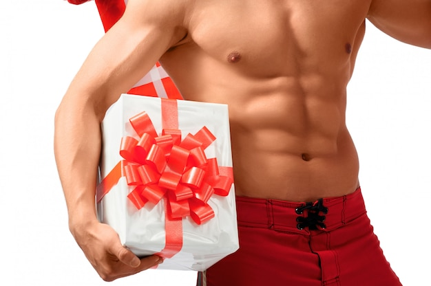 Geerntete nahaufnahme eines sexy hemdlosen mannes, der großes geschenk hält. Premium Fotos