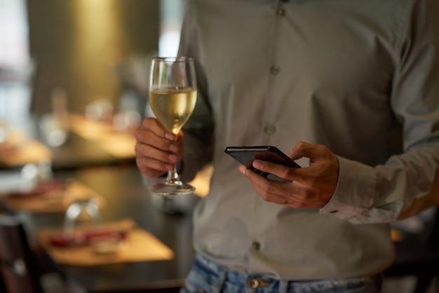 Geernteter mann, der das telefon hält sektkelch an einer party überprüft Kostenlose Fotos