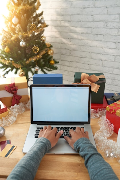 Geernteter mann, der onlinekäufe auf laptop vor weihnachten abschließt Kostenlose Fotos