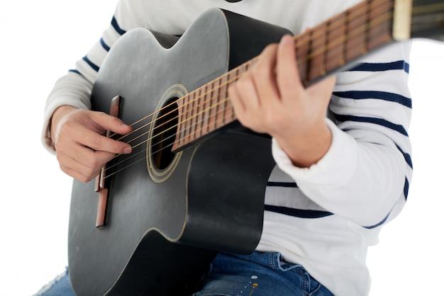 Geernteter nicht erkennbarer mann, der die akustikgitarre spielt Kostenlose Fotos