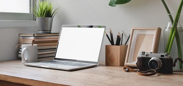 Geernteter schuss des bequemen arbeitsplatzes mit laptop-computer, büroartikeln und kamera des leeren bildschirms Premium Fotos