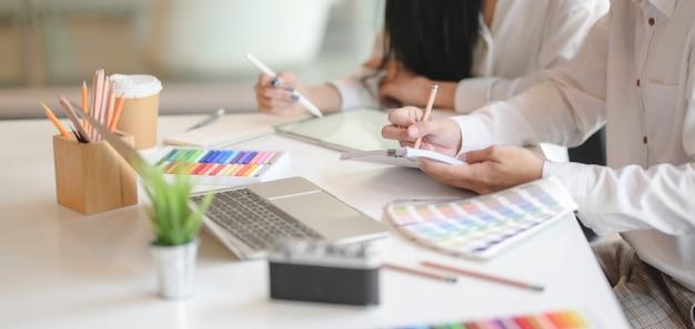 Geernteter schuss des grafikdesigners team ihre idee im modernen büro zusammen austauschend Premium Fotos