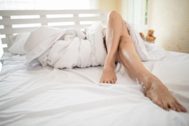 Geerntetes bild des beines liegend auf schöner frau des betts im schlafzimmer Kostenlose Fotos