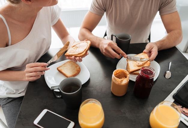 Geerntetes bild von paaren frühstücken geschmackvoll in der küche Kostenlose Fotos