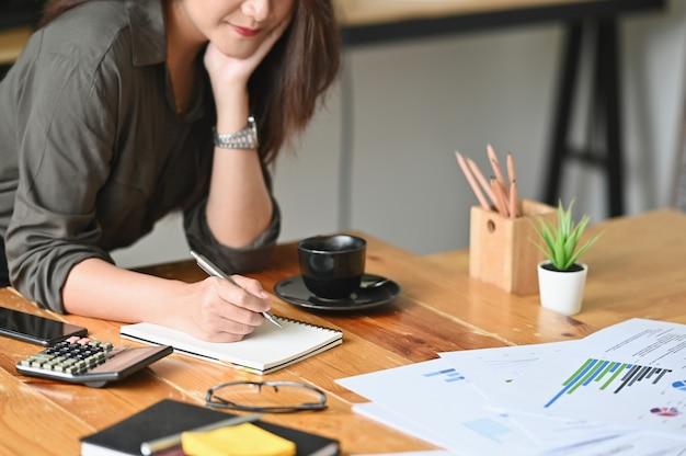 Geerntetes weibliches schreiben des schusses bezüglich der notizbuch- und finanzdaten bezüglich der tabelle. Premium Fotos