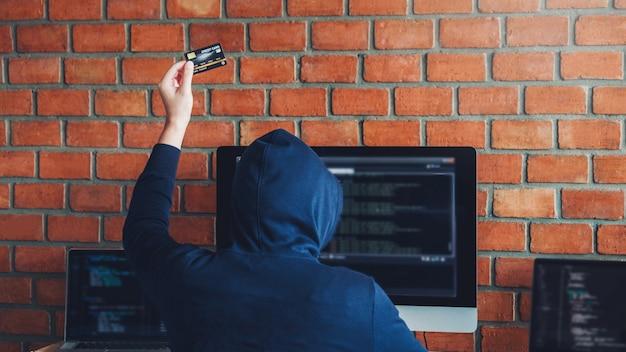 Gefährlicher mit kapuze hacker, der die kreditkarte verwendet, die schlechte daten in computeron-line-system schreibt und zu den globalen gestohlenen persönlichen informationen verbreitet. cyber-sicherheitskonzept Premium Fotos