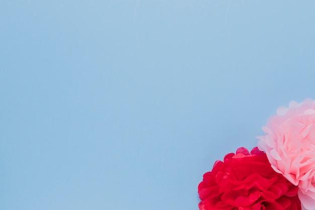 Gefälschte rosa und rote schöne dekorative blumen an der ecke des blauen hintergrundes Kostenlose Fotos